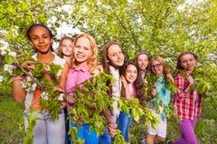Grupo de muchachas en jardín de la manzana de la primavera Foto de archivo libre de regalías