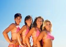 Grupo de muchachas felices en bikiníes imagenes de archivo
