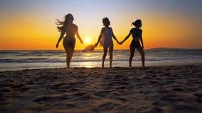 Grupo de muchachas felices que corren y que juegan en la arena en la puesta del sol Imagen de archivo libre de regalías