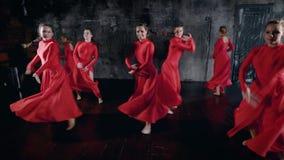 Grupo de muchachas hermosas en el baile rojo todo del vestido junto en un estudio, ensayo de la danza del grupo almacen de metraje de vídeo