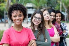 Grupo de muchachas internacionales que se colocan en línea Fotografía de archivo libre de regalías