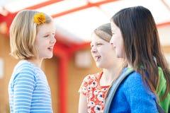 Grupo de muchachas que hablan fuera de la construcción de escuelas imagenes de archivo