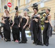 Grupo de muchachas que presentan en vestidos del diseñador Foto de archivo