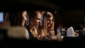 Grupo de muchachas que se encuentran para el almuerzo en el restaurante almacen de video