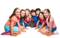 Muchachos y muchachas que se sientan junto en semicírculo Imagen de archivo libre de regalías