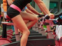 Grupo de muchachos y de muchachas en el gimnasio: Entrenamiento con las bicis de giro Fotos de archivo