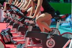 Grupo de muchachos y de muchachas en el gimnasio: Entrenamiento con las bicis de giro Imagen de archivo