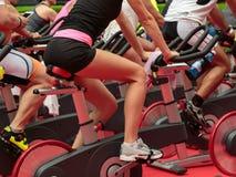 Grupo de muchachos y de muchachas en el gimnasio: Entrenamiento con las bicis de giro Fotografía de archivo libre de regalías
