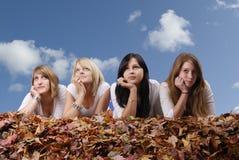 Grupo de mujer joven que miente en hojas de otoño foto de archivo libre de regalías