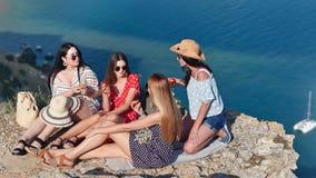 Grupo de mujer joven relajada feliz del viaje que disfruta de la rotura que tiene comida campestre encima de la montaña sobre el  metrajes