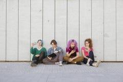 Grupo de mujeres adolescentes que usan la tecnología que se sienta en el isolat del piso Imagen de archivo