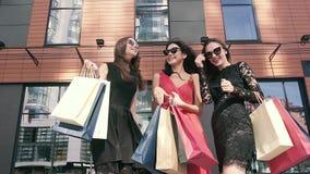 Grupo de mujeres alegres que disfrutan de su día acertado de las compras en la ciudad almacen de metraje de vídeo