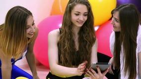 Grupo de mujeres caucásicas alegres jovenes que usan la tableta en un ajuste almacen de metraje de vídeo
