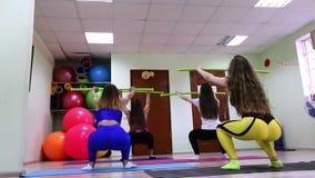 Grupo de mujeres caucásicas jovenes que hacen ejercicios con el palillo que se coloca en estudio de la aptitud almacen de metraje de vídeo