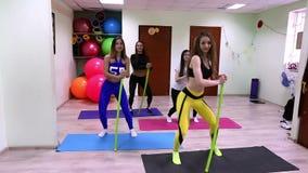 Grupo de mujeres caucásicas jovenes que hacen ejercicios con el palillo que se coloca en estudio de la aptitud metrajes