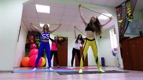 Grupo de mujeres caucásicas jovenes que hacen ejercicios con el palillo que se coloca en estudio de la aptitud almacen de video