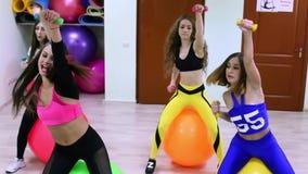 Grupo de mujeres caucásicas jovenes que hacen ejercicios con los fitballs y pesas de gimnasia en un club de fitness almacen de video