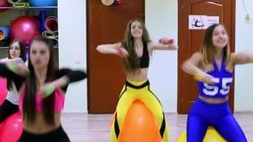 Grupo de mujeres caucásicas jovenes que hacen ejercicios con los fitballs y pesas de gimnasia en un club de fitness metrajes