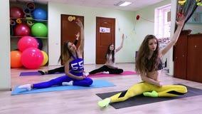 Grupo de mujeres caucásicas jovenes que hacen estirando sentarse en el piso en estudio de la aptitud metrajes