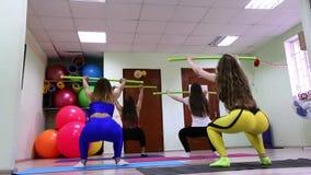 Grupo de mujeres caucásicas jovenes que hacen los ejercicios sentar-UPS en un club de fitness almacen de metraje de vídeo