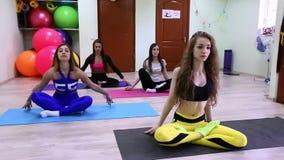 Grupo de mujeres caucásicas jovenes que meditan sentarse después de entrenar en estudio de la aptitud almacen de video
