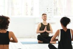 Grupo de mujeres con el instructor de sexo masculino que se sienta en las esteras de la yoga fotografía de archivo