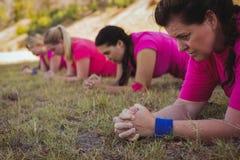 Grupo de mujeres del ajuste que ejercitan en el campo de bota Fotografía de archivo