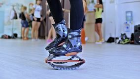 Grupo de mujeres deportivas jovenes que hacen ejercicios de los fitnes con los zapatos de los saltos del kangoo en un gimnasio metrajes