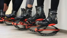 Grupo de mujeres deportivas jovenes que hacen ejercicios de los fitnes con los zapatos de los saltos del kangoo en un gimnasio almacen de video
