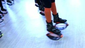 Grupo de mujeres deportivas jovenes que hacen ejercicios de los fitnes con los zapatos de los saltos del kangoo en un gimnasio almacen de metraje de vídeo