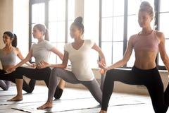 Grupo de mujeres deportivas jovenes que practican yoga, haciendo anjaneyasana imagenes de archivo