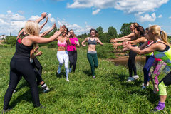 Grupo de mujeres emocionadas que cruzan el finshline un maratón que corre en tierra herbosa en parque Fotos de archivo libres de regalías