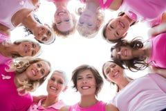 Grupo de mujeres felices en el rosa que lleva del círculo para el cáncer de pecho Foto de archivo libre de regalías