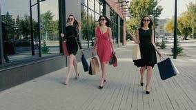Grupo de mujeres jovenes atractivas que caminan a lo largo de ventanas de la tienda Cámara lenta almacen de metraje de vídeo