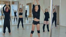 Grupo de mujeres jovenes deportivas que ejercitan en el estudio, calentándose antes de clase de danza del polo metrajes