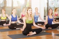 Grupo de mujeres jovenes en clase de la yoga Imagenes de archivo