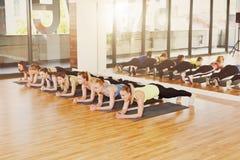 Grupo de mujeres jovenes en la clase de la aptitud, ejercicio del tablón Foto de archivo