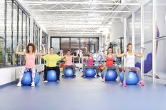 Grupo de mujeres jovenes hermosas que se resuelven en bolas azules de los pilates Foto de archivo libre de regalías