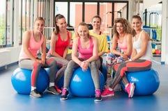 Grupo de mujeres jovenes hermosas que se resuelven en bolas azules de los pilates Fotografía de archivo