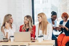 Grupo de mujeres jovenes que discuten proyecto creativo durante proceso del trabajo imagen de archivo libre de regalías
