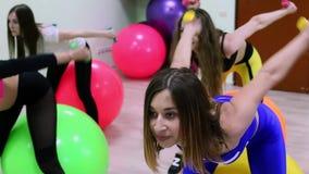 Grupo de mujeres jovenes que hacen ejercicios con pesas de gimnasia en club de fitness almacen de video