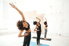 Grupo de mujeres jovenes que hacen la yoga que estira ejercicios foto de archivo libre de regalías