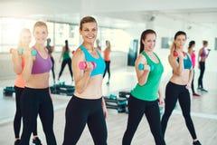 Grupo de mujeres jovenes que hacen pesas de gimnasia Fotos de archivo libres de regalías
