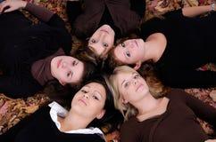 Grupo de mujeres jovenes que mienten en hojas de otoño Fotografía de archivo libre de regalías