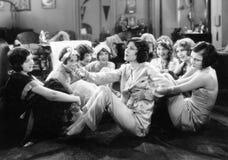 Grupo de mujeres jovenes que se sientan en el piso de hablar de la sala de estar (todas las personas representadas no son un ning Fotos de archivo libres de regalías