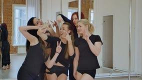 Grupo de mujeres jovenes que toman un selfie durante una clase de danza del polo Imagen de archivo libre de regalías