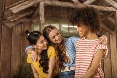 Grupo de mujeres jovenes sonrientes hermosas que se colocan de abarcamiento en el pórtico Imágenes de archivo libres de regalías