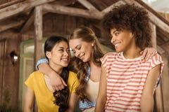 Grupo de mujeres jovenes sonrientes hermosas que se colocan de abarcamiento en el pórtico Imagen de archivo