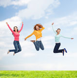 Grupo de mujeres jovenes sonrientes que saltan en aire imagenes de archivo