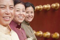 Grupo de mujeres maduras en la ropa tradicional que se coloca al lado de la puerta del chino tradicional Fotografía de archivo libre de regalías